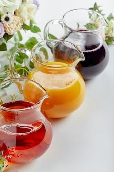 이벤트 케이터링에 다양한 주스가 담긴 주전자. 사과, 오렌지, 체리, 토마토 주스.