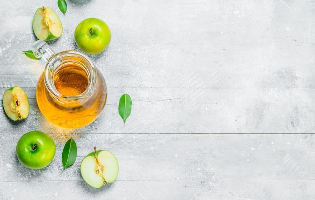 リンゴのスライスとガラスの瓶にジュースと新鮮なリンゴ。白い素朴な背景に。