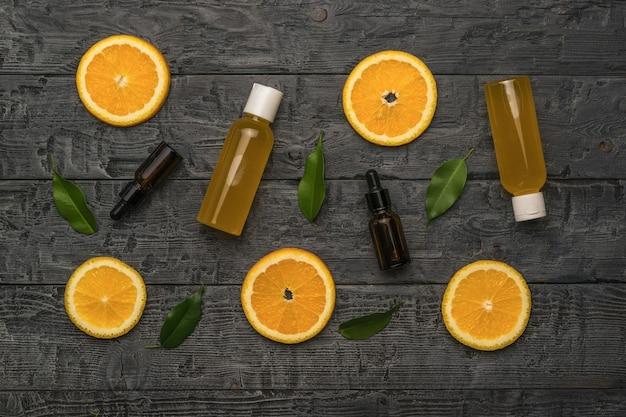 주스 병, 의료 병, 오렌지 잎 및 나무 배경 조각. 자연 요법 치료의 개념입니다.