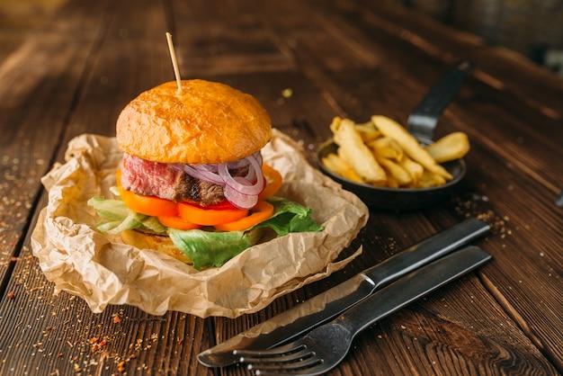 Бургер с соком и стейком на деревянном столе крупным планом
