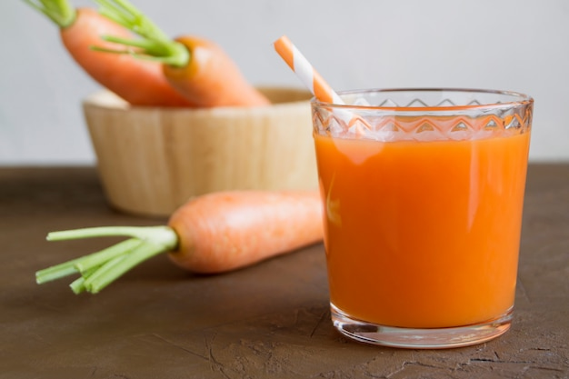 Juice of fresh ripe carrots on a brown background.