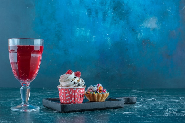 A juice glass next to cupcakes on blue background. high quality photo