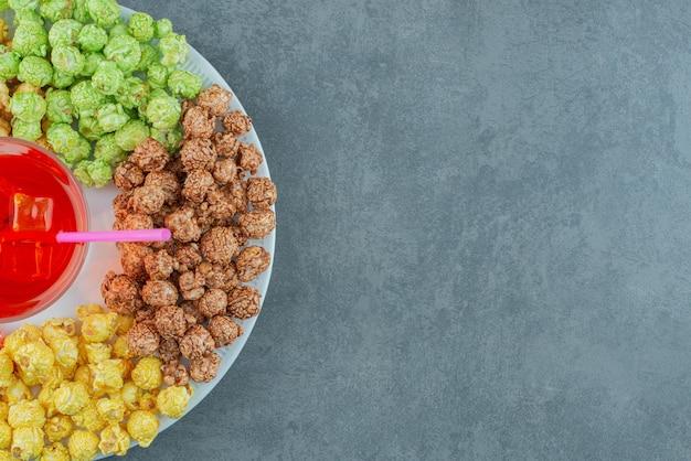대리석 배경에 다양한 팝콘 사탕 접시 한가운데에 있는 주스 유리. 고품질 사진