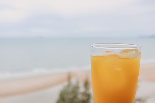 Juice in a glass with sea view background in concept of summer
