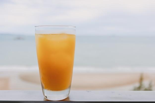 여름의 개념에 바다 전망을 배경으로 유리에 주스