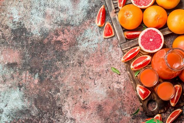 ピッチャーのジュースとまな板のグレープフルーツのかけら。素朴な背景に