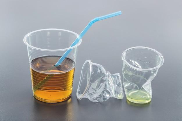 Сок в стакане с соломинкой. рядом два использованных пластиковых стаканчика. крупный план.