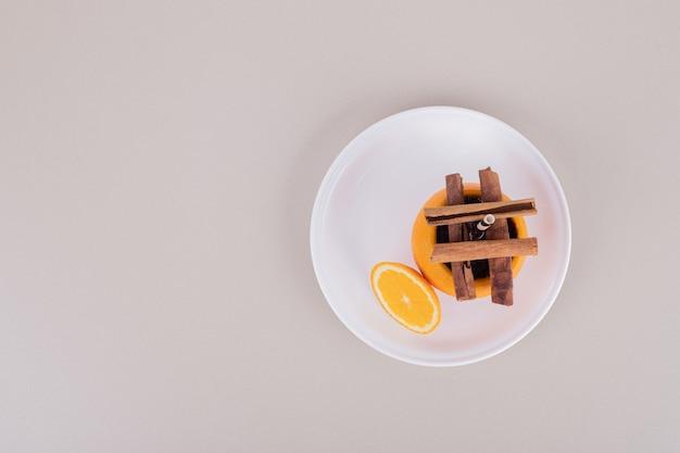Succo d'arancia con cannella sul piatto bianco