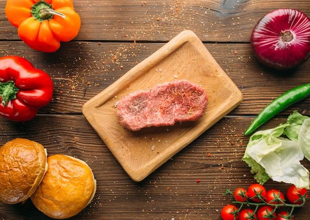 Сок кусок мяса в приправе и свежие овощи на деревянном столе, вид сверху, никто. сырой стейк, перец и зелень, приготовление пищи