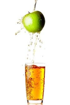 白い壁に隔離されたガラスにリンゴから注ぐジュース