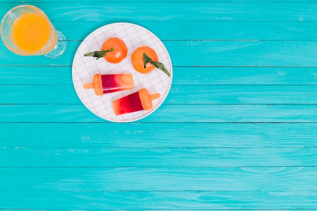 Juice and tangerines and popsicle on plate on wooden surface