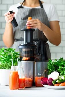 과즙 짜는기구와 당근 주스. 깨끗한 식사, 해독 개념