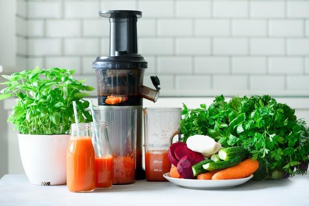 Соковыжималка и морковный сок. чистая еда, концепция детоксикации
