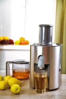Соковыжималка и грушевый сок на кухонном столе