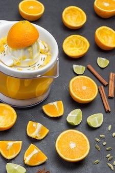 ジュースとジューサー、上にオレンジの皮。スライスしたオレンジとドライジンジャー、シナモンスティック、スターアニスをテーブルに。黒の背景。上面図。