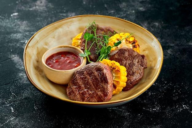 Сочные и аппетитные стейки из телятины с курицей гриль и овощной сальсой, подаются в тарелке на темной поверхности