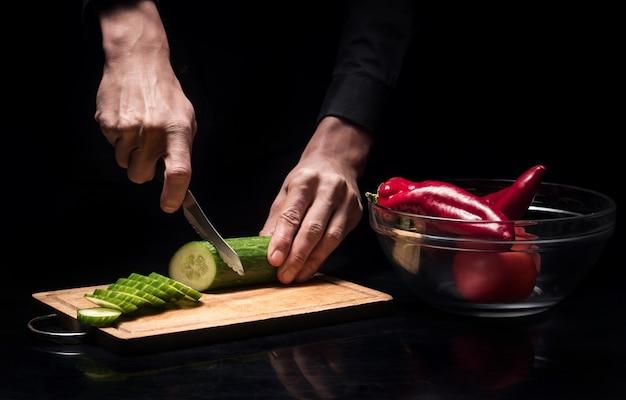 맛있고 건강합니다. 닫기 젊은 요리사 망 손 오이 및 피망을 사용 하 고 레스토랑에서 요리하는 동안 신선한 야채를 자르고.