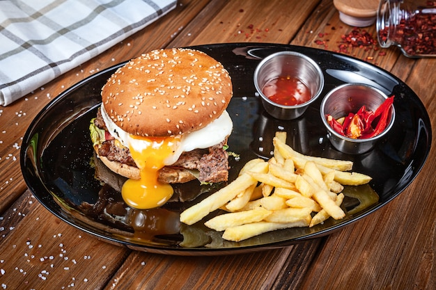 Сочный и вкусный бургер с яйцом, салатом и соусом на черной тарелке с картофелем фри. американский фаст фуд. гамбургер с копией пространства на деревянных фоне. крупным планом, селективный фокус. еда. гриль-меню