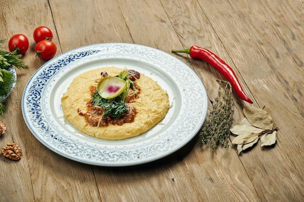 Polenta, 옥수수 죽 반찬과 육즙과 특이한 이스라엘 치킨 스테이크 (pargiyot). 구운 치킨. 목재 표면