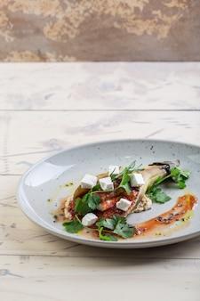ジューシーで食欲をそそる焼きナスとトマトとハーブを白いお皿にのせてレストランでお召し上がりいただけます。