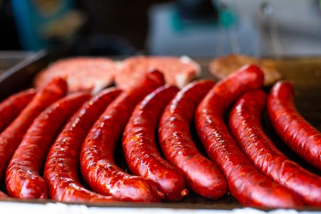 Сочные аппетитные колбаски гриль на металлическом подносе. прилавок уличной еды.