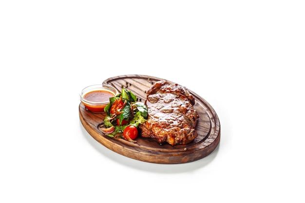 Сочный аппетитный стейк на гриле с салатом на деревянной доске.
