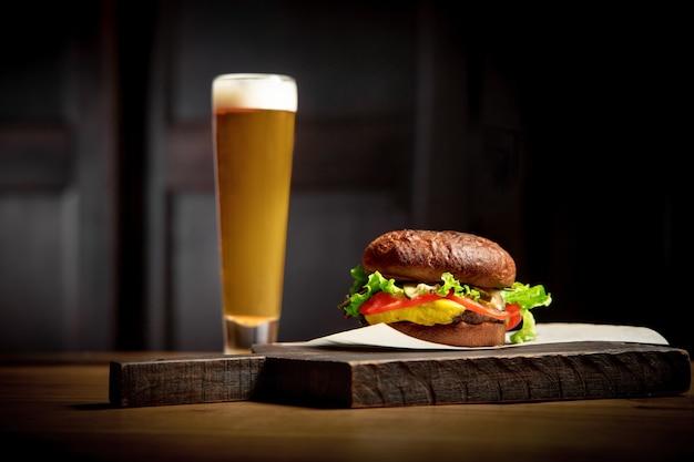 Сочный аппетитный традиционный бургер с пивом на фоне деревянной доски