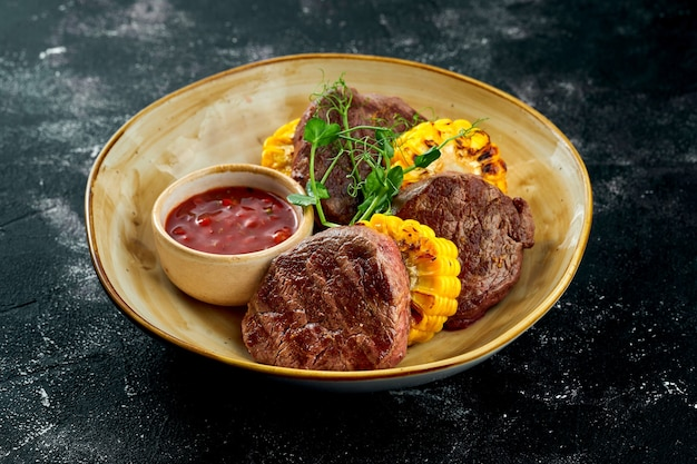 Juicy and appetizing veal steaks with grilled chicken and vegetable salsa, served in a plate on a dark surface