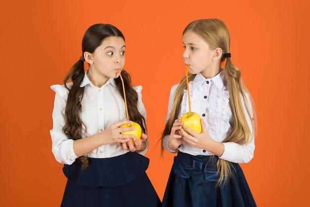 과즙이 많은 사과. 건강한 사과 간식을 먹는 학교 아이들. 사과를 들고 귀여운 여 학생입니다. 학교 간식 휴식을 취하는 어린 소녀. 천연 비타민 음식을 먹는 어린 소녀들. 과일에는 비타민이 풍부합니다.