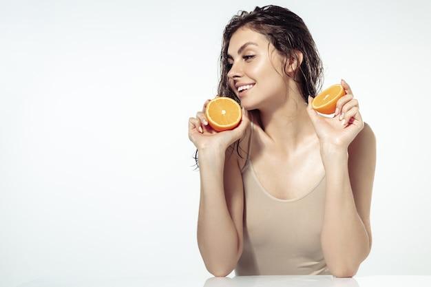 흥미 진진한. 흰 벽에 얼굴 근처에 오렌지 조각으로 아름 다운 젊은 여자. 화장품, 메이크업, 자연 및 환경 치료, 피부 관리의 개념. 빛나고 건강한 피부, 패션, 헬스케어.