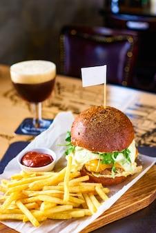 ジューシーなビーフバーガー、フライドポテト、レストランでの軽めのビール