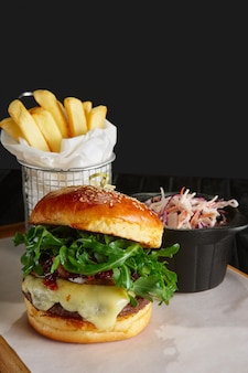 Juicy beef burger with lingonberry sauce, melted cheese, arugula served with fried potato and red cabbage