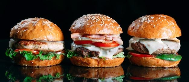 Сочные говяжьи гамбургеры на черном фоне.