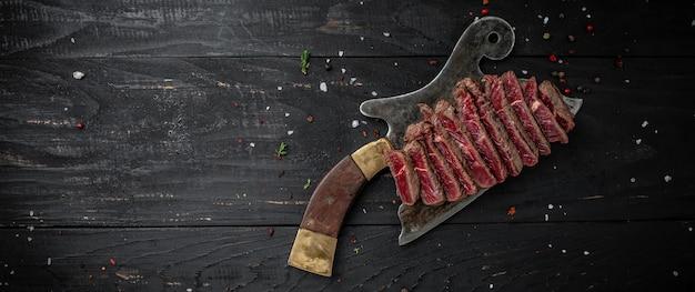 Сочный стейк из говяжьей крупы из мраморной говядины средней прожарки, подается на старом мясном мясе на темном деревянном фоне. формат длинного баннера, вид сверху.
