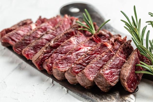Сочный стейк из говяжьей крупы из мраморной говядины средней прожарки, подается на старом мясном мяснике на светлом фоне, вид сверху.