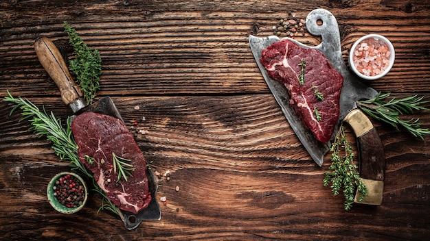 木製の背景、長いバナー形式、上面図の古い肉屋で提供される生の大理石の牛肉からのジューシーなビーフランプステーキ。