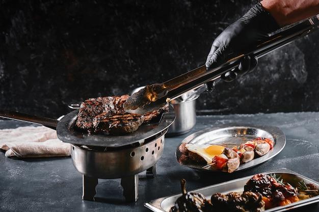ジューシーなビーフステーキがバーベキューの炎、ライフスタイル、食べ物の写真、コピースペースでバク転します