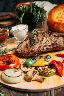 Juicy beef steak with grilled vegetables on board