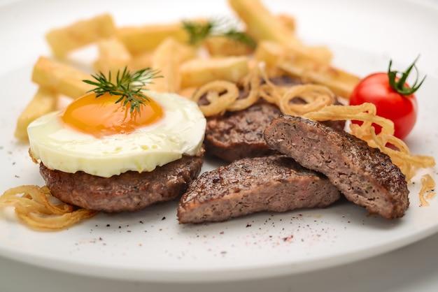 ジューシーなビーフステーキ、トマト、ゆで卵、ジャガイモ