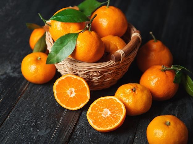 Juicy bright ripe tangerines in wooden basket on dark background