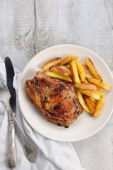 튀긴 감자와 뼈에 육즙, 갈색 돼지 고기 스테이크