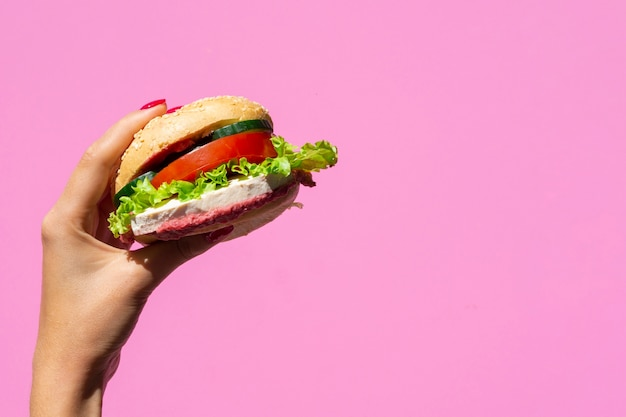 Juicy burger on pink background with copy space