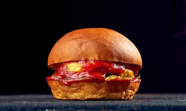 Сочный бургер с говядиной, сыром, огурцом и помидорами, соусом на темном фоне.