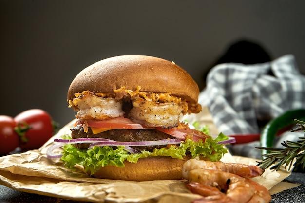 暗いテーブルの上に牛肉、エビ、トマト、チーズ、シャキッとした玉ねぎが入ったジューシーなハンバーガー。クローズアップ、セレクティブフォーカス