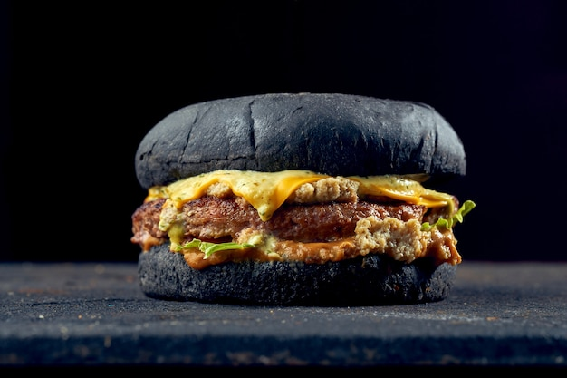 Сочный бургер с черными булочками с говядиной, сыром, огурцом и томатным соусом на темном фоне.