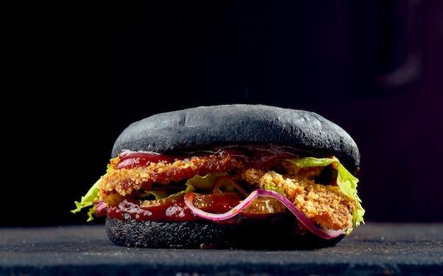 Сочный бургер с черными булочками с куриными наггетсами, сыром, огурцом и томатным соусом на темном фоне.