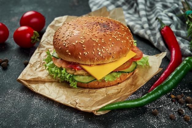 Сочный бургер с курицей, помидорами, сыром и хрустящим луком на темном столе. бургер с курицей
