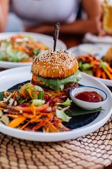 Juicy burger with fresh vegetables in cafe on table