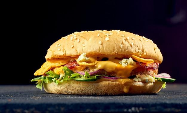 Сочный бургер со свининой, сыром, яйцом, огурцом и помидорами, соусом на темном фоне.