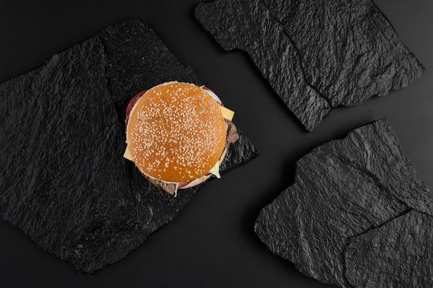 黒い石のプレートの背景にジューシーなチーズバーガー。上からの眺め